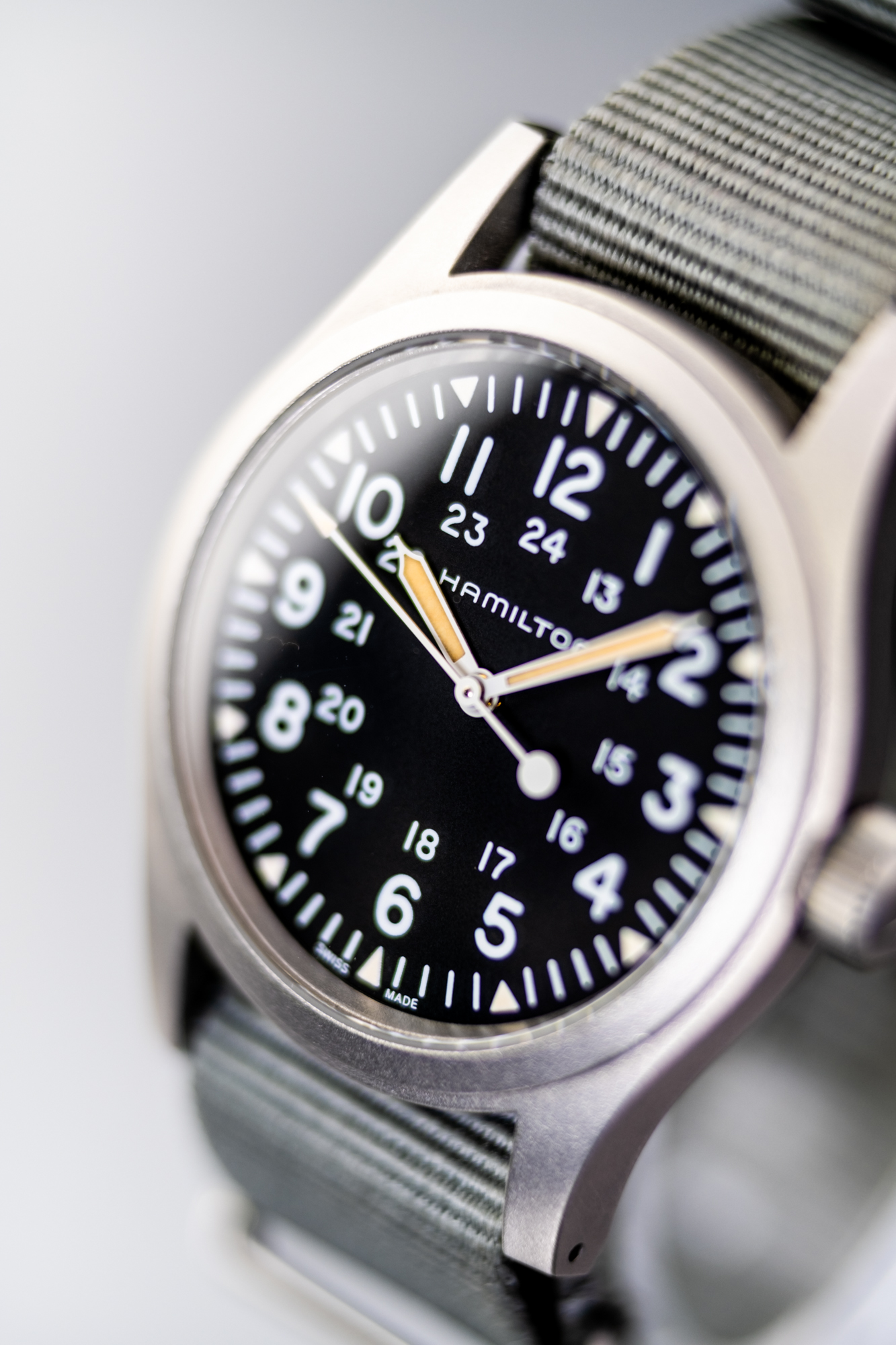 The Hamilton Khaki Field Mechanical H69439931with BluShark NATO Strap shows selective focus and reflections that give shape to its sapphire crystal.