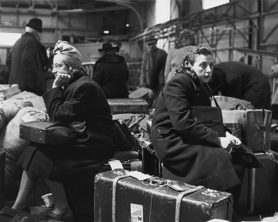 Two women sitting on luggage at the docks, from the Displaced Persons series 1947-48