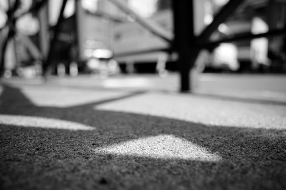 Grains of sidewalk concrete are the only points of focus in this ground level NYC street scene.