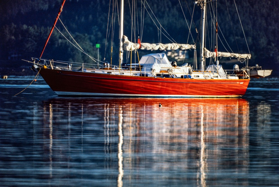 Morning sunlight glistens off the hull of a cherry-red schooner, in Bar Harbor, Maine.