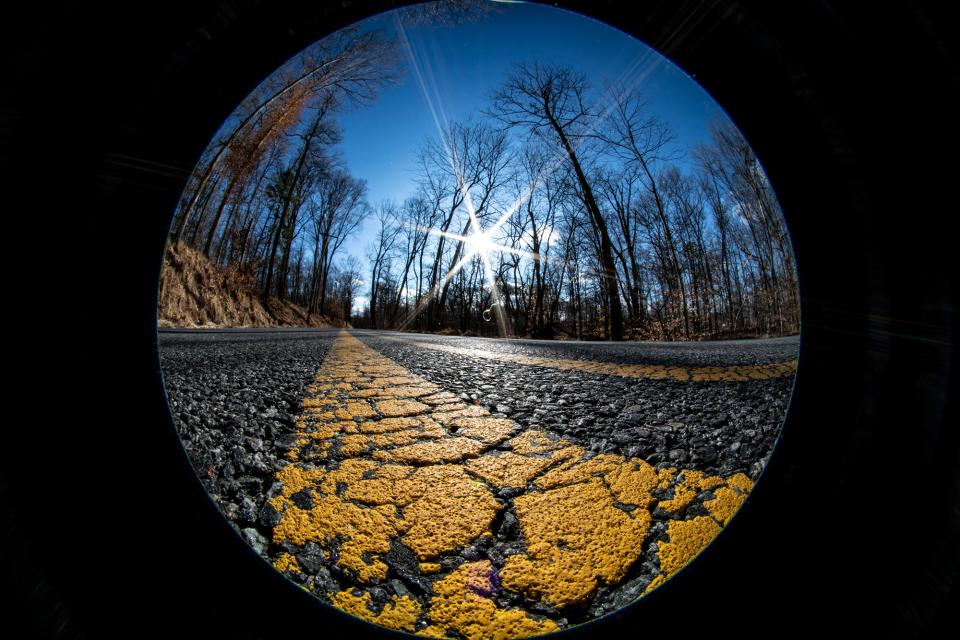 By shooting at ground level, I was able to play the textured yellow stripe in the road against the blue of the sky. A starburst from the sun is a total bonus that helps make for a graphically dynamic image.