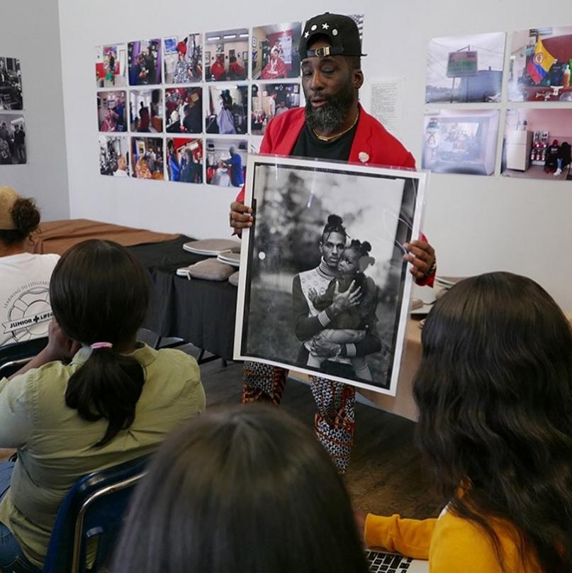 Brooklyn photographer Russell Frederick displays a darkroom print to workshop participants while discussing his 20-year-plus project photographing the residents of his Bedford Stuyvesant neighborhood, August 2019.