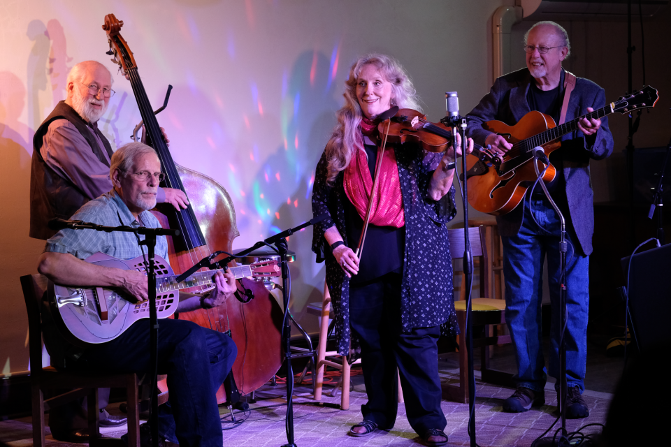 (From left) The late Roger Anderson, along with LJ Mattingly, Joy Ward, and Mark Clark kick off a tune at the Farmer's Mercantile Hall. LJ sat in on resophonic guitar with the others, whose bluegrass band is called Castle Ridge.