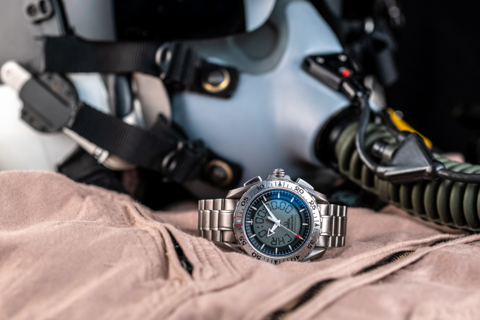 A bit of reflection on the Omega Speedmaster Professional X-33 Ref 3291.50.00 shown with a nomex desert tan flight suit, US Navy HGU-68/P flight helmet, and MBU-12/P oxygen mask.