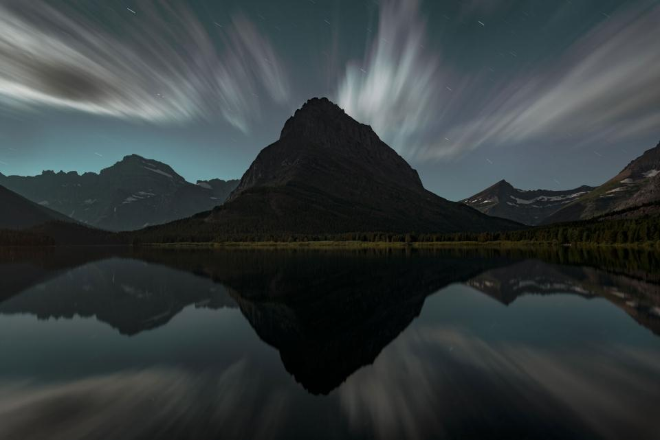 Moonrise behind a silhouetted peak, Glacier National Park, Montana.