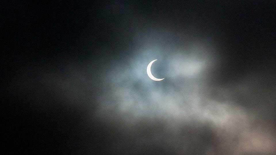 A partial solar eclipse breaks through the clouds over San Diego. ©Todd Vorenkamp