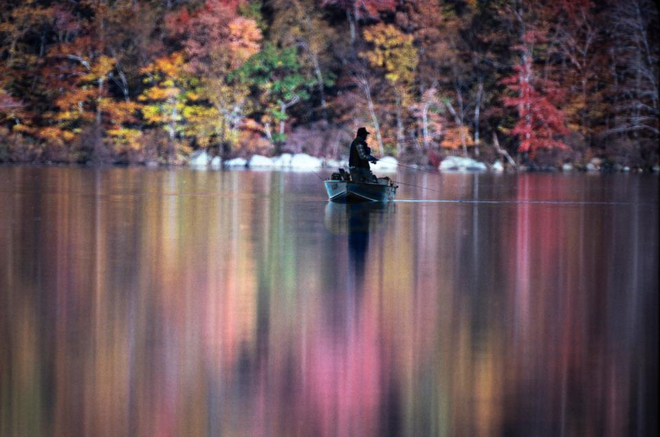 Fall colors surround a lone fisherman out on a lake.