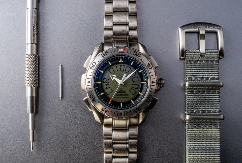 I created a stage here with the Omega Speedmaster Professional X-33 Ref 3291.50.00 sporting its titanium bracelet, a BluShark NATO Strap, a spring bar, and a Bergeon 6767 spring bar tool.