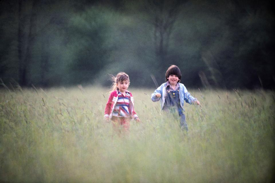A couple of cute kids running through a field appear sharp against ethereally blurred trees in the background and tall grass in the foreground when captured with a 500mm mirror lens.