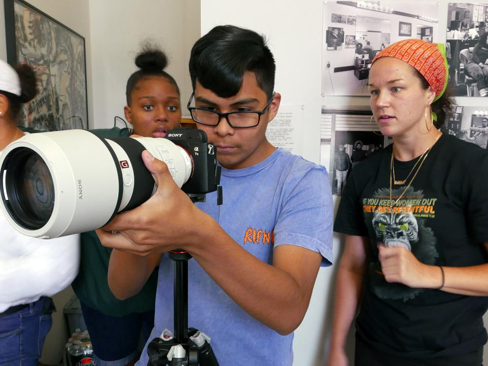 Madeleine Budd, B&H Photo Marketing Specialist, demonstrating the use of a telephoto lens to 2019 Everyday Newburgh workshop participants Leiyana Gayle and Diego Quispe.
