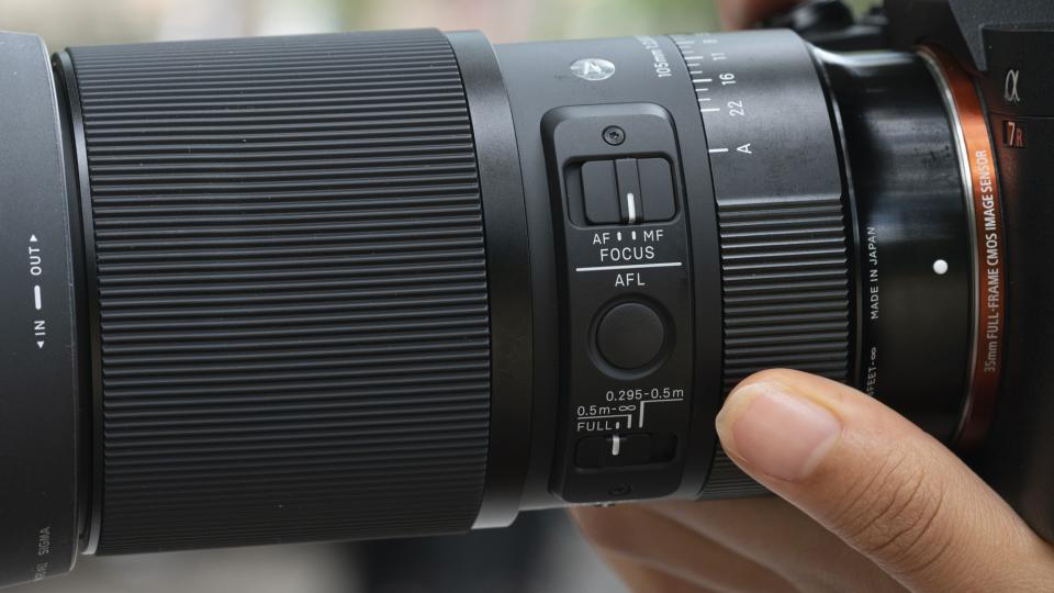 The lens includes four switches (AF/MF, Focus Limiter, Aperture Lock, and Aperture Click) and an AFL button for quickly adjusting settings.