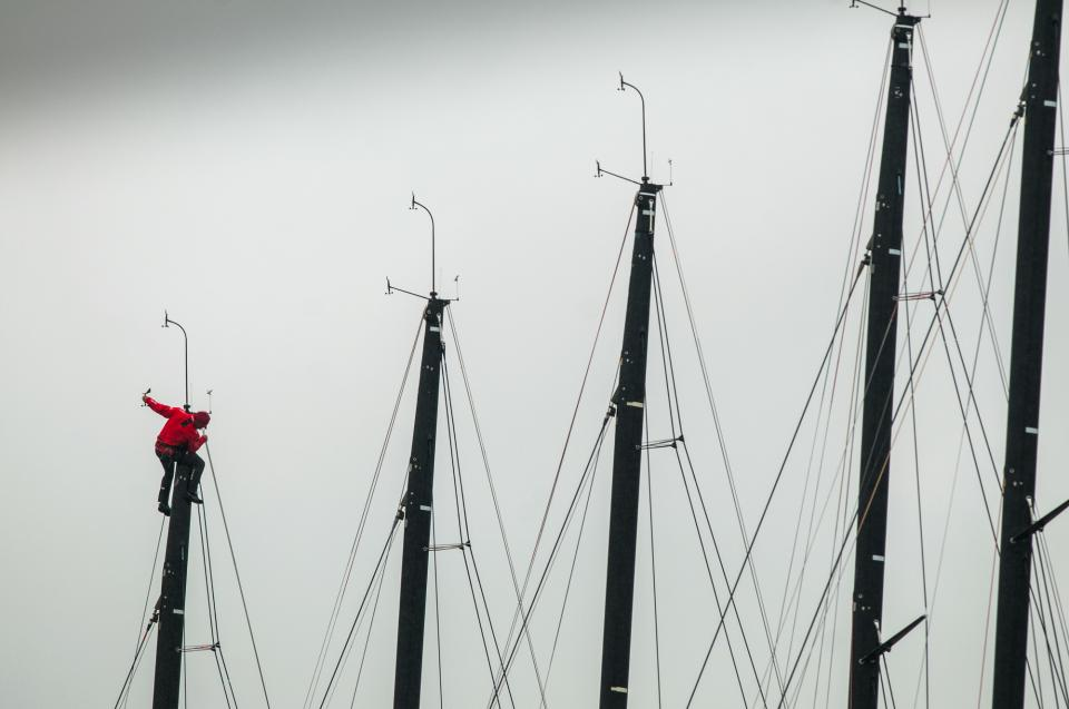 Are these masts on small or large sailboats? Large, based on the size of the sailor hoisted aloft.